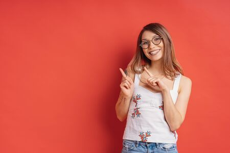 Positive smiling young female with glasses, points aside with cheerful expression, shows something amazing at blank space, isolated over red backgroud. Advertisement