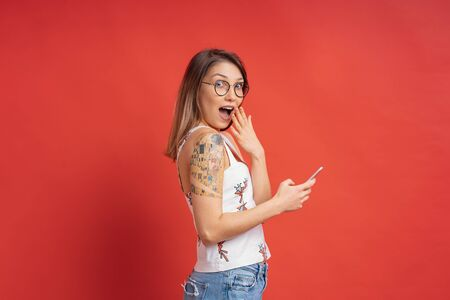 Surprised smiling young woman with a phone in hands on red background in the studio, side view. Modern youth concept.