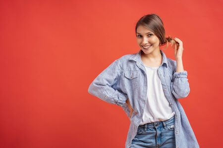 Portrait of pretty casual young woman playing with her hair isolated on red background with copy space.