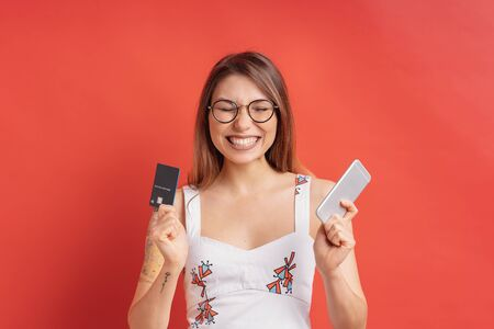 Image of happy, glad, excited pretty young woman isolated over red background holding a mobile phone in one hand and credit card in another.