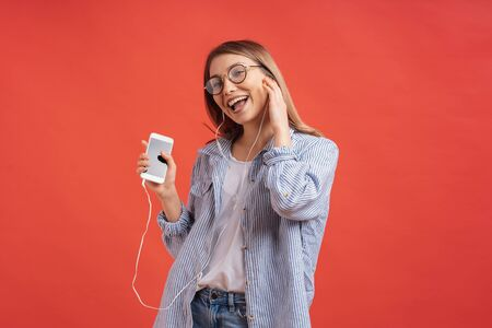 Charming girl in casual clothes and earphones dancing, moving hands, smiling, enjoying the moment isolated on red background.