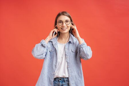 Portrait of an attractive casual young woman smiling with earphones and glasses isolated on red background