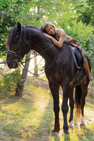 Young woman in a bright colorful dress riding a black horse in the park Stock Photo