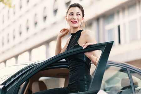 Sensual laughing woman standing with a feline look in the door of a car wearing a stylish black romper, elegant bun and red lips