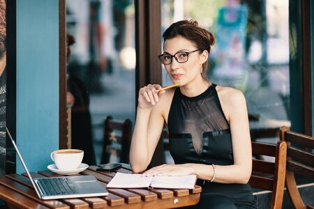 Woman and technology. Refined business woman sitting at table in cafe with windows in the background taking notes on a notebook. Fashion Blogger.