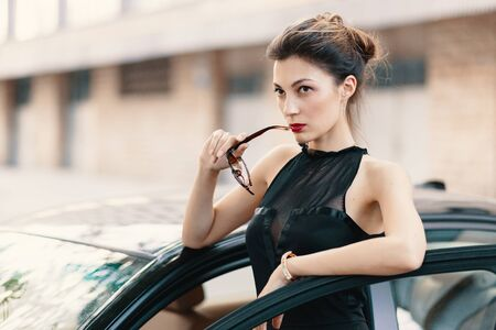 Confident dangerous woman standing with a feline look in the door of a car, elegant bun and red lips with a blurred building in perspective.