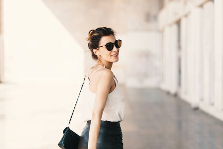 Beautiful smiling young woman in sunglasses wearing leather clutch and skirt, white easy blouse and looking away over the shoulder