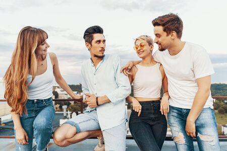 Grupo de amigos disfrutando al aire libre en la azotea. Jóvenes amigos al atardecer en el patio del ático