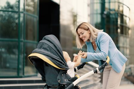 Portrait of a successful business woman in blue suit with baby. Business woman pushing baby stroller 스톡 콘텐츠