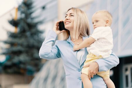 Successful business woman in blue suit with baby. Successful mother in business walking with baby in her hands and talking on cellphone