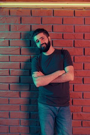 Cheerful young man in a nightclub at a brick wall. Neon light