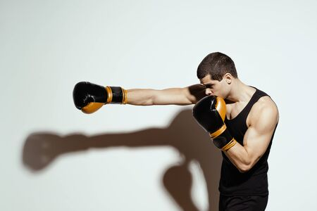 Sportsman boxer fighting throwing a punch with the right hand creating a shadow on the white background. 写真素材