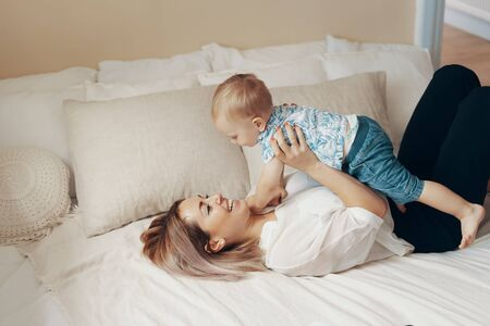 Young mother with her child working in bedroom at home. Business mom takes a break. Multi-tasking, freelance and motherhood concept Stockfoto