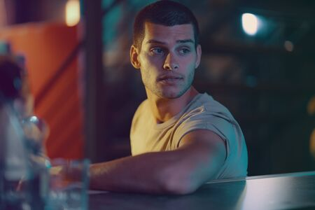 Close-up portrait of attractive male model. Retro wave portrait of a young man in a bar. Model in colorful bright neon lights.