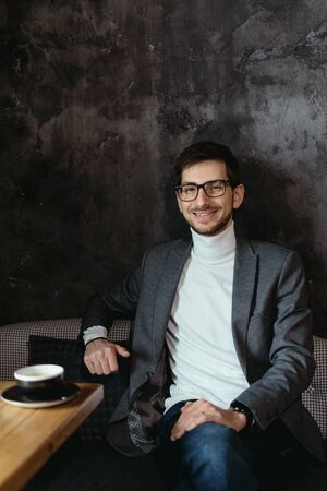 Young, successful businessman wearing glasses, gray jacket, white turtleneck on dark gray background Banque d'images - 144165856