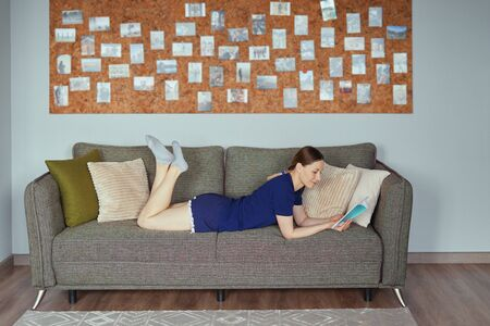 A beautiful Caucasian woman reading a book while resting on the sofa for indoor leisure activity at home. After work lifestyle for people