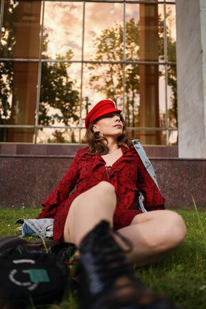 A modern young woman in red dress, denim jacket and red cap, posing on the street of the city with glass windows reflecting trees in background. Beauty, street fashion.