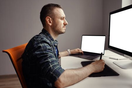 Graphic Designer working with interactive pen display, digital Drawing tablet and Pen on a computer with blank monitor