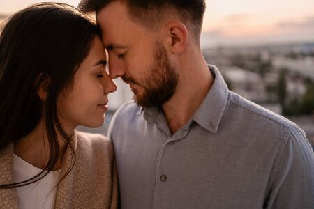 Close up portrait, man and woman smiling to each other on sunset with city in background. Couple romantic intimate moments