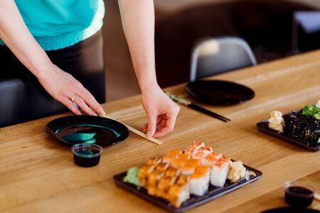 Woman hands arranging the table with various sushi sets on a wood table in a sunny home