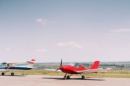 Small propeller sport airplane in the field waiting to take off with sky in background. Private airplanes