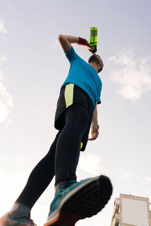 Low angle view of a sportsman drinking water with sky in background Imagens