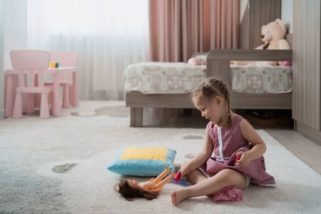 Cute little girl playing with a doll whille sitting on the carpet in her room