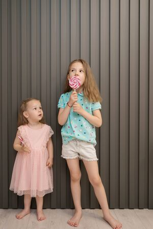 Happy young caucasian little girls kids lick eat happy big sweet lollypop candy on gray striped background