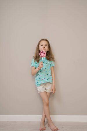 Happy young caucasian little girl kid with happy big sweet lollypop candy on beige background