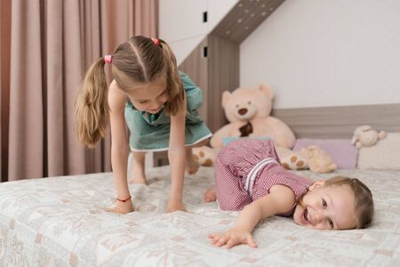 Happy funny little girls having fun on bed feeling joy, cheerful cute active kids having fun playing laughing in bedroom