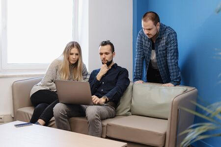 Small soft meeting area in chill out zone of office with three persons having there work meeting or conversation at the table, Two men and one woman