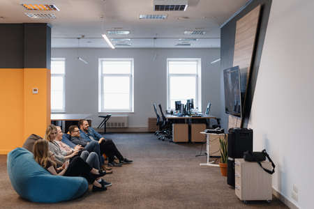 A cheerful team Play video games on the console while relaxing on beanbags after work