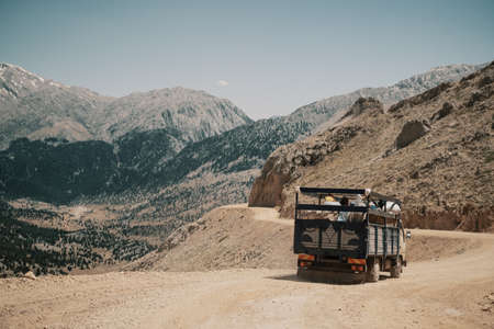 Classic brown big rig semi truck with step down turn on winding road going through the mountains.