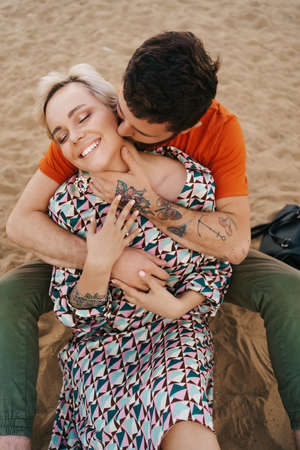 Man kissing tenderly his wives neck hugging her with beautifully tattoed hands while relaxing on the sand