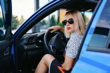 Confident and beautiful woman in sunglasses. Rear view of attractive young female in casual wear driving a car Stock Photo
