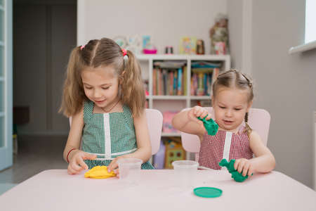 Little girls with lovely faces play with clay molding shapes, learning through playing with colored plasticine developing creativity