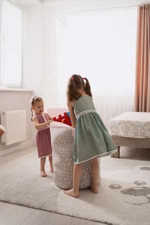 Hard to decide who will get the toys. Cute little sisters playing in their sunny room Banque d'images