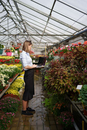 Smiling Greenhouse owner posing with a laptop in her hands talking on the phone having many flowers in background and glass roof. Space for text on screen.