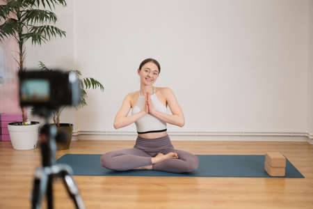 Portrait of beautiful young woman practicing yoga indoor