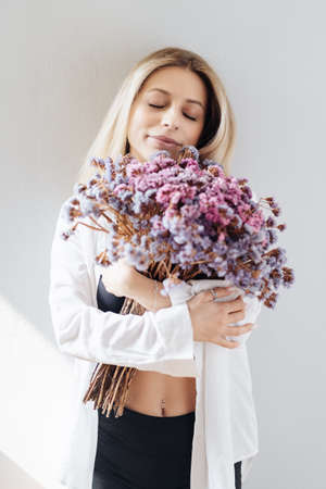 Portrait of a beautiful young girl in white shirt, black top and shorts, holding a big bouquet of dried flowers over gray background splashed by lines of light