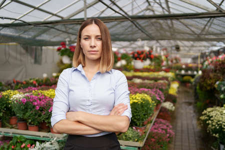 Greenhouse owner posing with folded arms having many flowers in background and a colleague holding a pot with pink chrysanthemums under glass roof