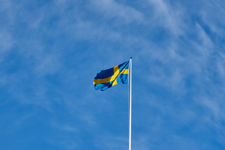 Flag of Sweden against a blue cloudy sky on a background.