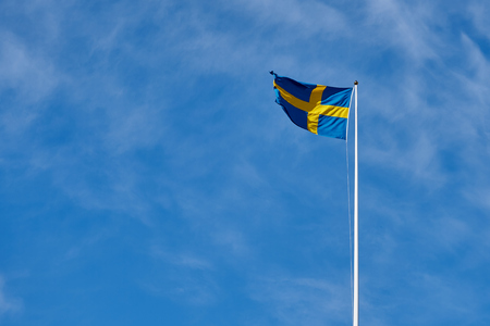 Flag of Sweden against a blue cloudy sky on a background. Copy space for text.