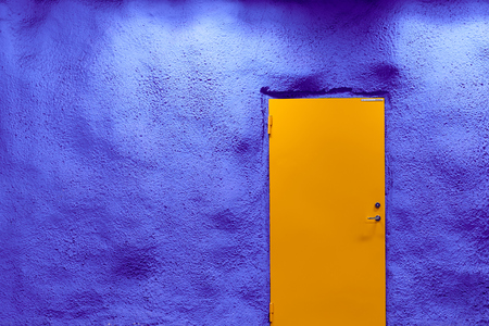 Orange door with ultramarine blue wall with shadows and lights. Copy space.
