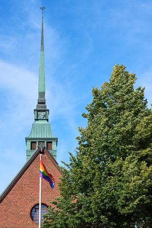 Rainbow flag and a church and blue sky on a background.
