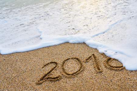 The year 2018 passed the concept. The wave of foam washes away the inscription 2018 written on the sand.