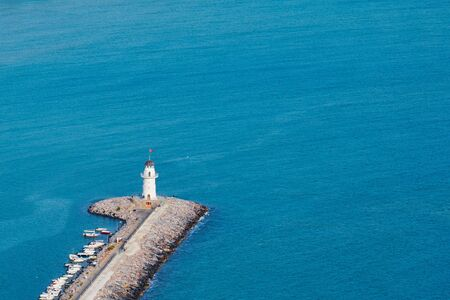 A lighthouse in harbor of Alanya, Turkey against a blue sea. Фото со стока