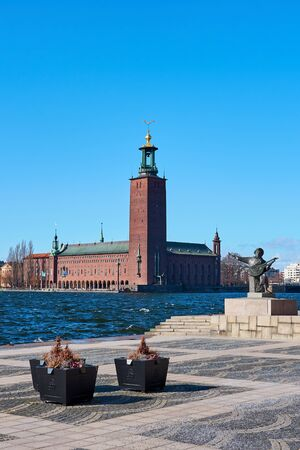 Stockholm city hall in daylight against a blue sky with waves on water.