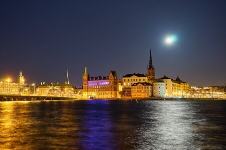 Old city of Stockholm with reflections of lights on water in nighttime.