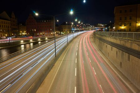 The night road in the city with lights and light trails of traffic.
